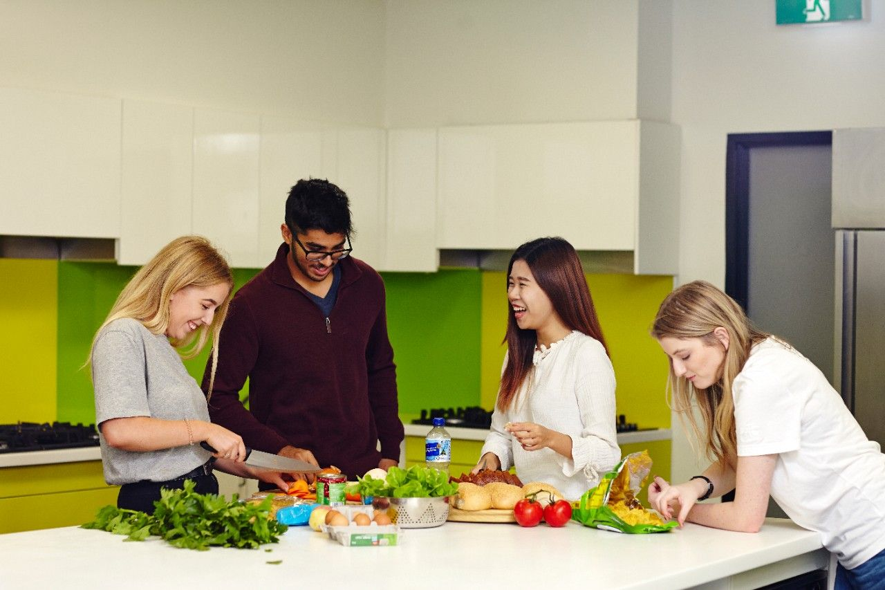 Four happy students in a test kitchen prepare a range of healthy food.