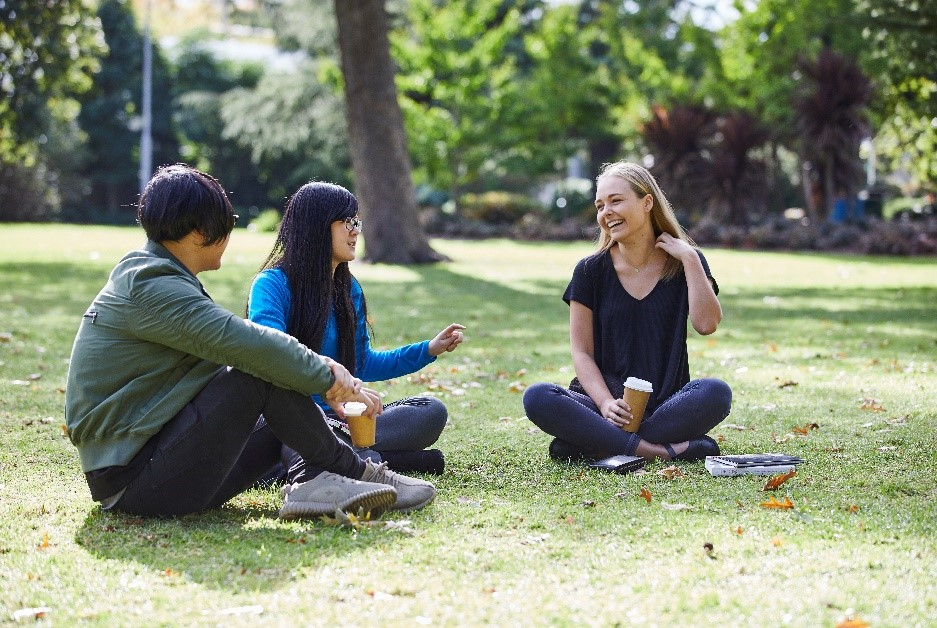 Three students sit in the park laughing and drinking coffee