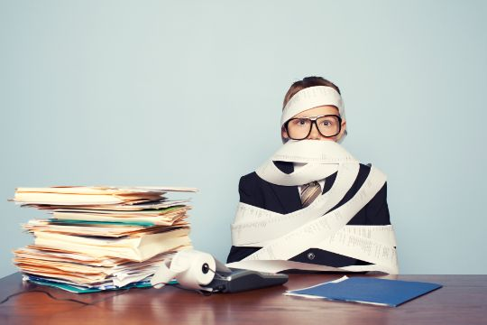 Boy Accountant Overworked and Covered in Paper