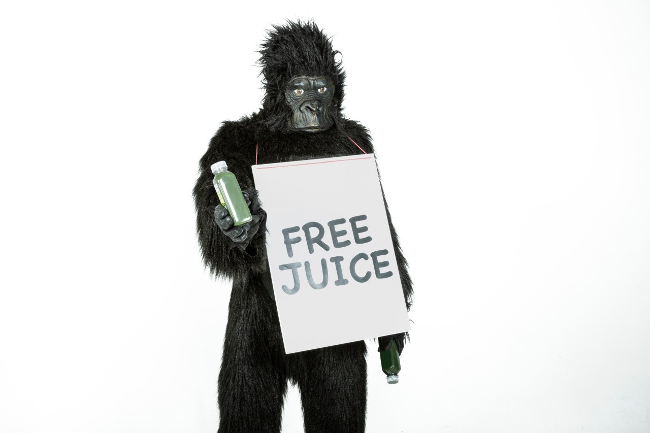 "A person in a gorilla suit with a sign that reads ""Free Juice"" offers a bottle of green juice"