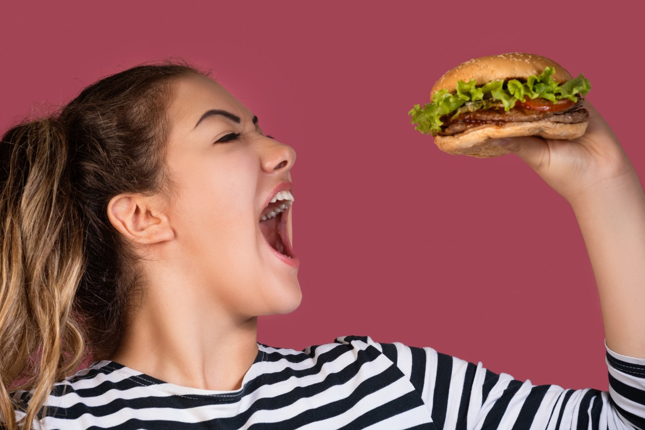 Hungry cool girl in striped t-shirt eating hamburger over pink background