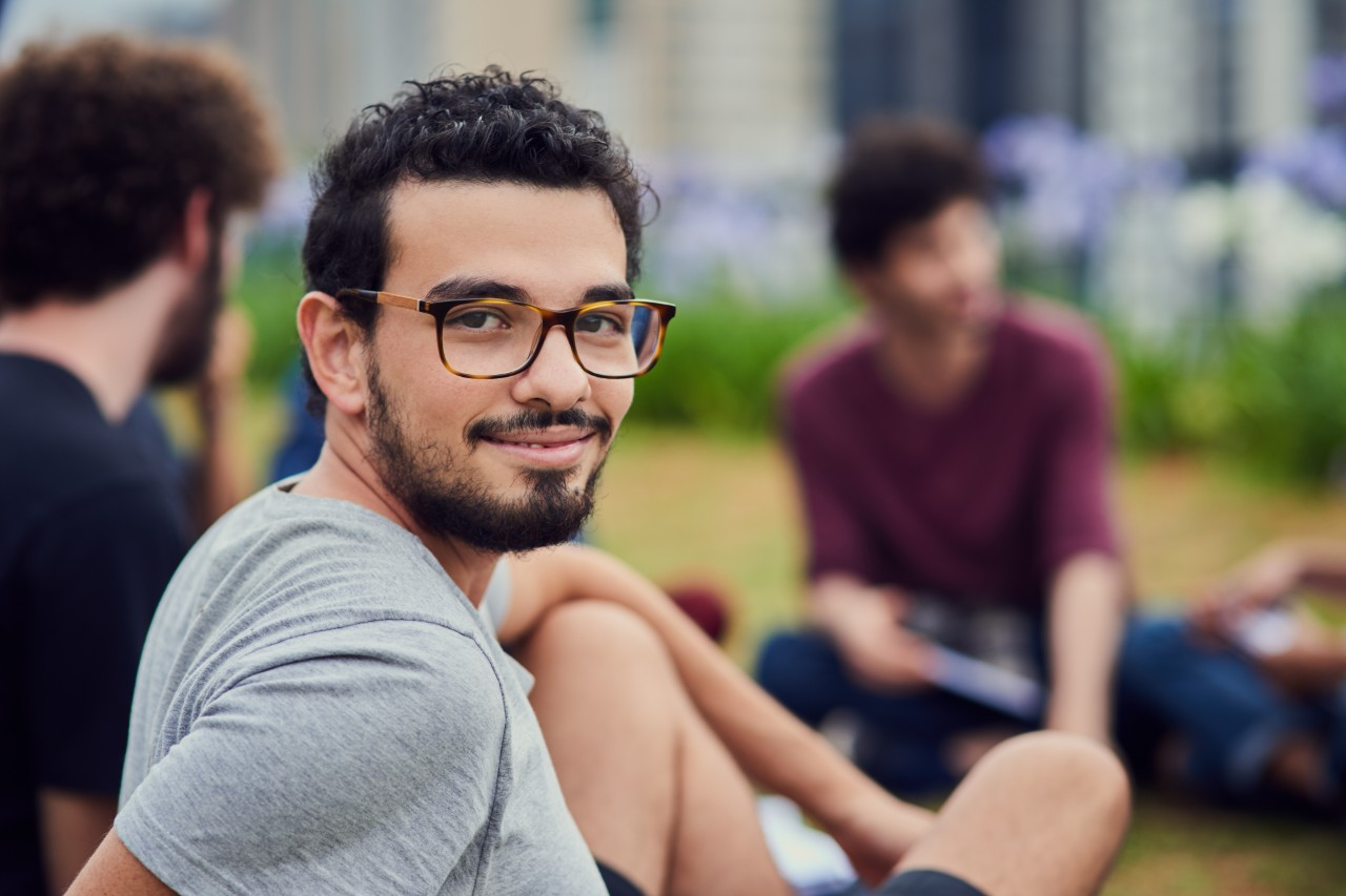 Portrait of a cheerful young man sitting in the park with his friends and studying outside during the day.