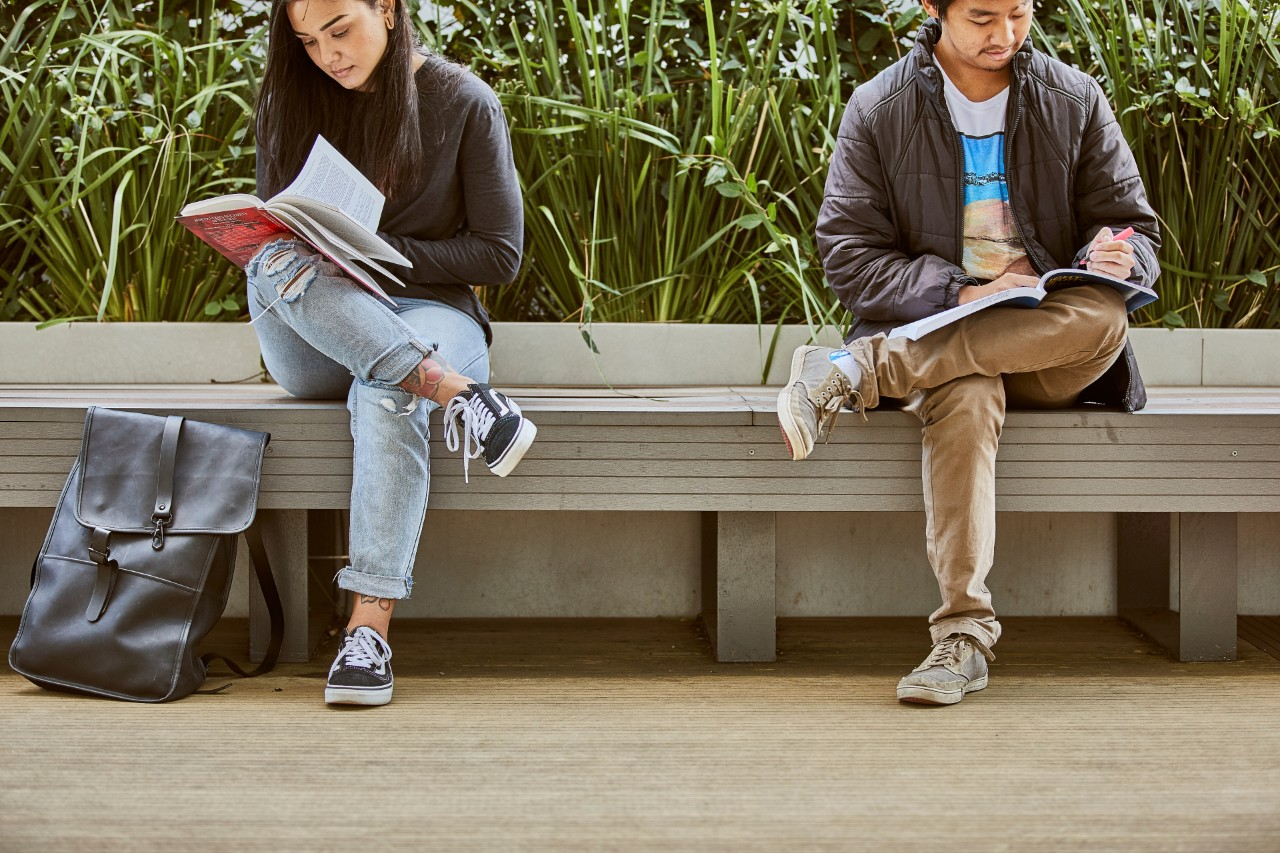 Two students enjoy the outdoor spaces of Swinburne's Hawthorn campus as they read course texts.