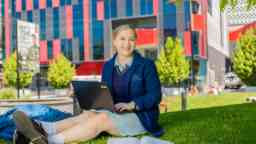 Girl in a high school uniform and laptop and books, sitting on grass outside The George Building in the Hawthorn campus