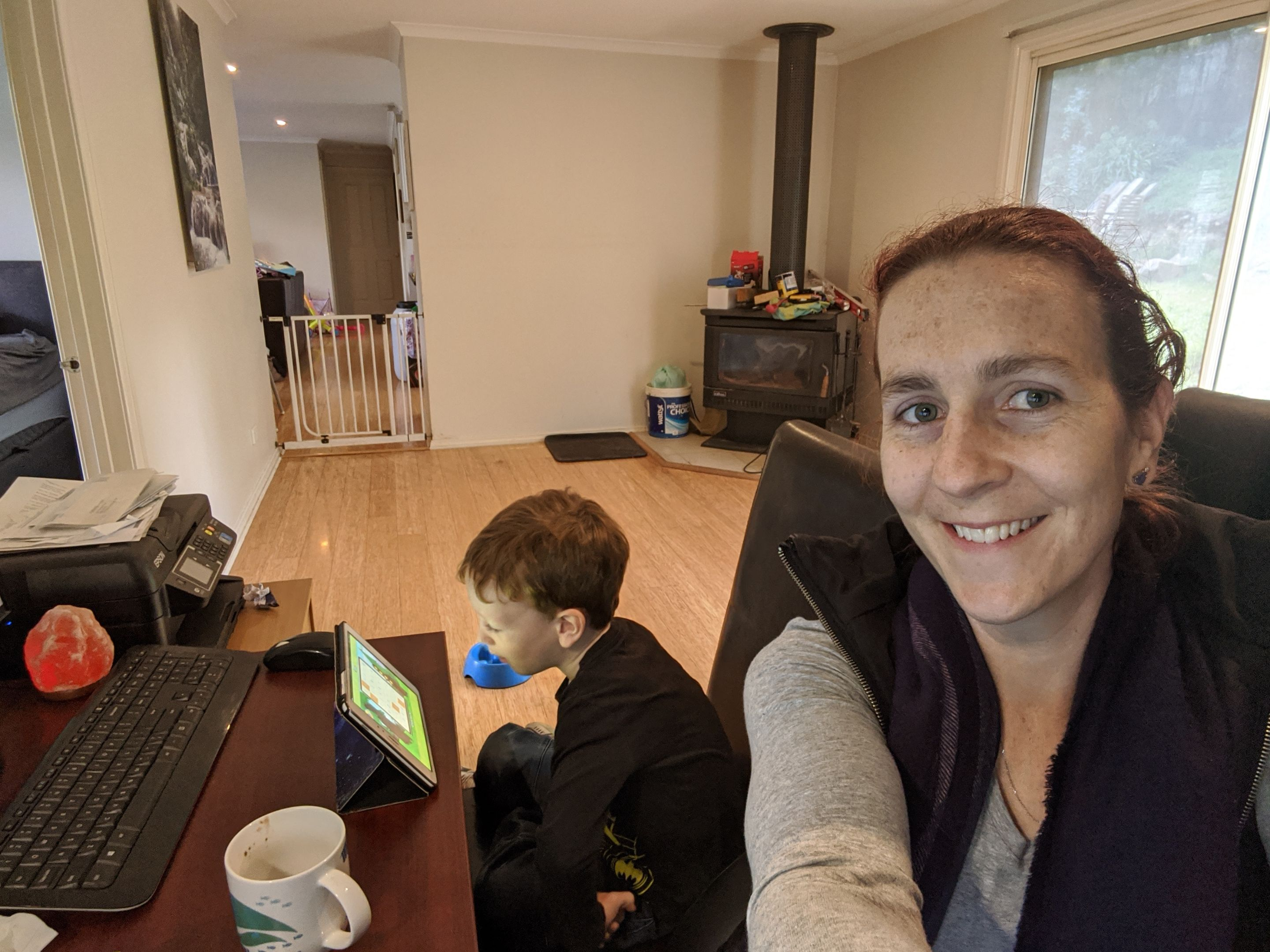 Diploma of Nursing Coordinator, Rachel Gilder working from home with her child pictured beside her looking at a tablet