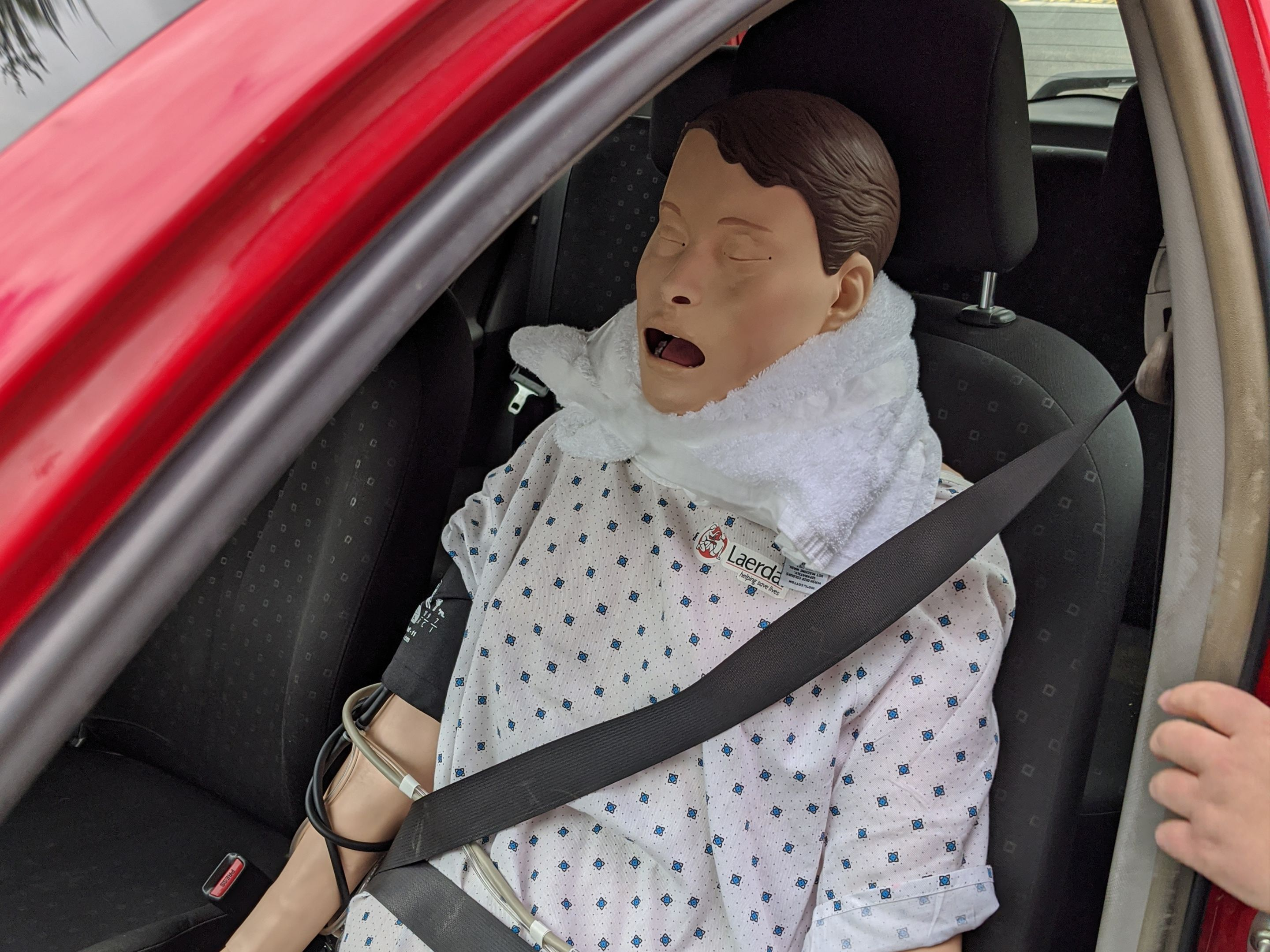 Nursing mannequin buklend in to a red car