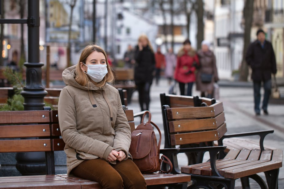 Woman in brown clothing sitting on a bench seat wearing a facemask