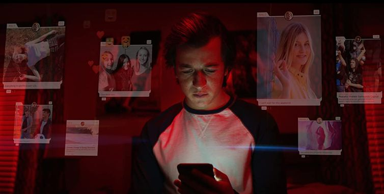 A still from the Netflix documentary The Social Dilemma with a young male looking at his smart phone