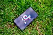 TikTok logo on a phone screen and phone is lying on the grass