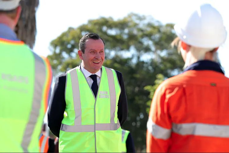 Western Australia Premier Mark McGowan wearing a high-visibility vest adressing some tradespeople