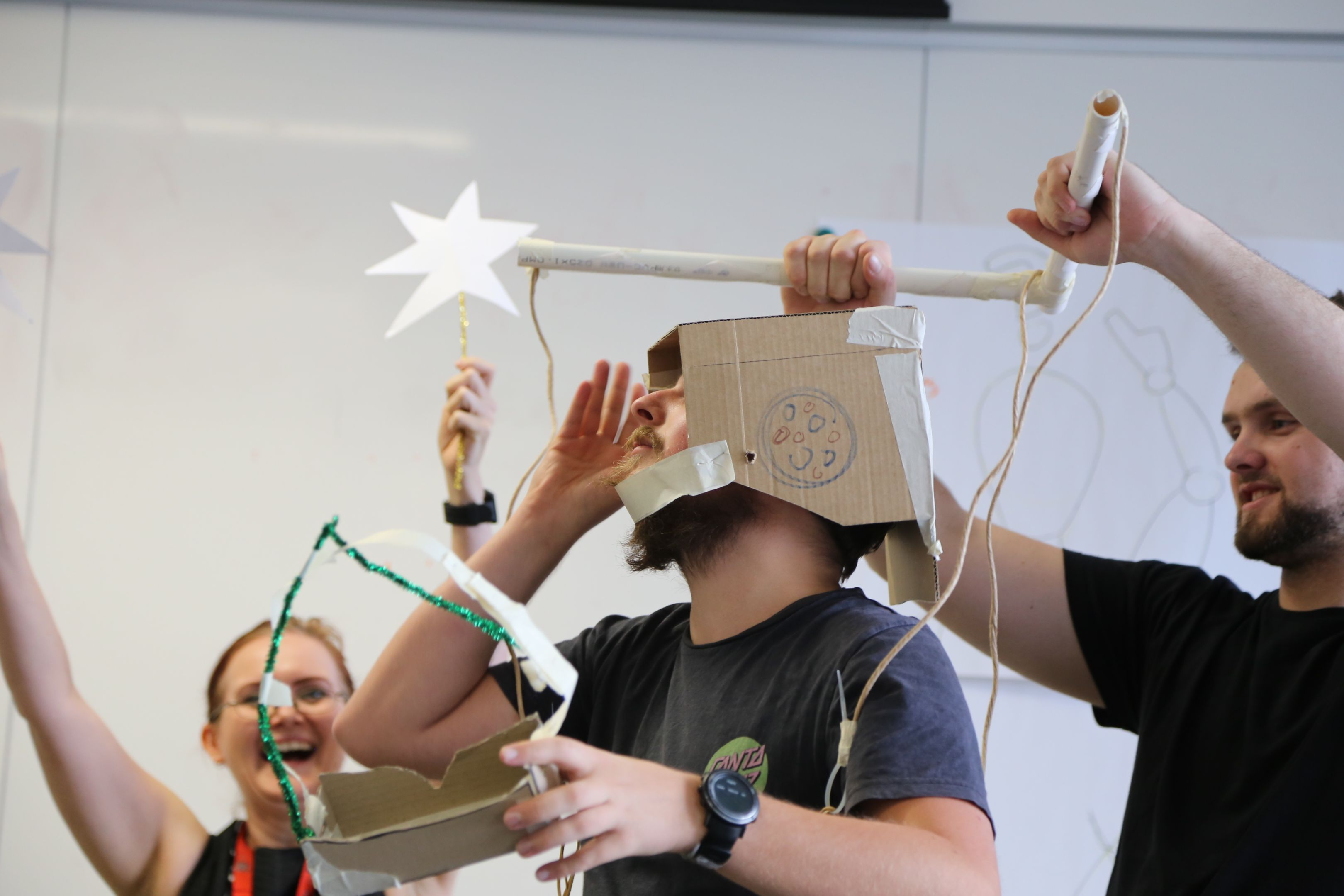 A group of students playing with cardboard.