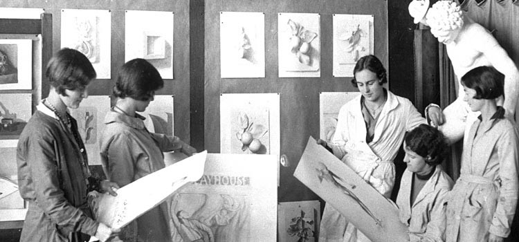 Old photograph of women looking at drawings