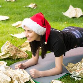 girl wearing santa hat exercising on mat