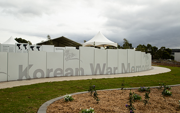 Melbourne's Korean War Memorial panels with images of Australian soldiers, text and floral emblems