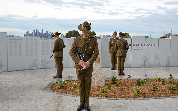 Australian soldier and graphics on perforated memorial panels, and soldiers at the opening