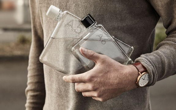 A person holds a memobottle close to their chest