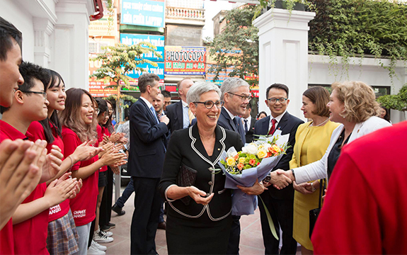 The Governor of Victoria greets people at the Swinburne Vietnam opening in Hanoi, holding a bouquet of flowers
