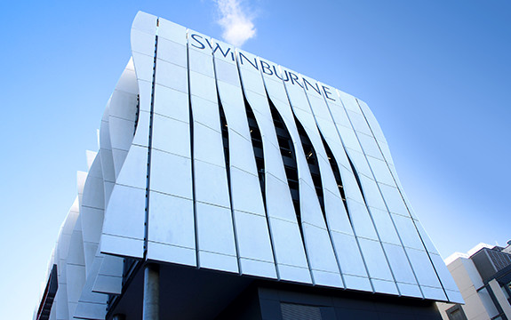 The large waved Swinburne signage of the Advanced Manufacturing and Design Centre building in Hawthorn which faces East down Burwood Road.