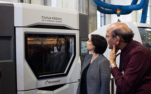 People inspect a 3D printer within the Factory of the Future