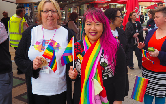 Two Swinburne staff members stand smiling, holding rainbow flags