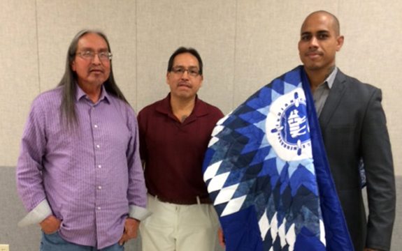 Stephane Shephers stands with two Native Americans