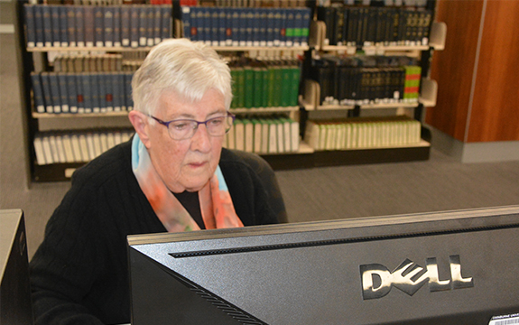 85-year-old Anne Scott is in the library at Swinburne in at a computer desk. She is using a computer.
