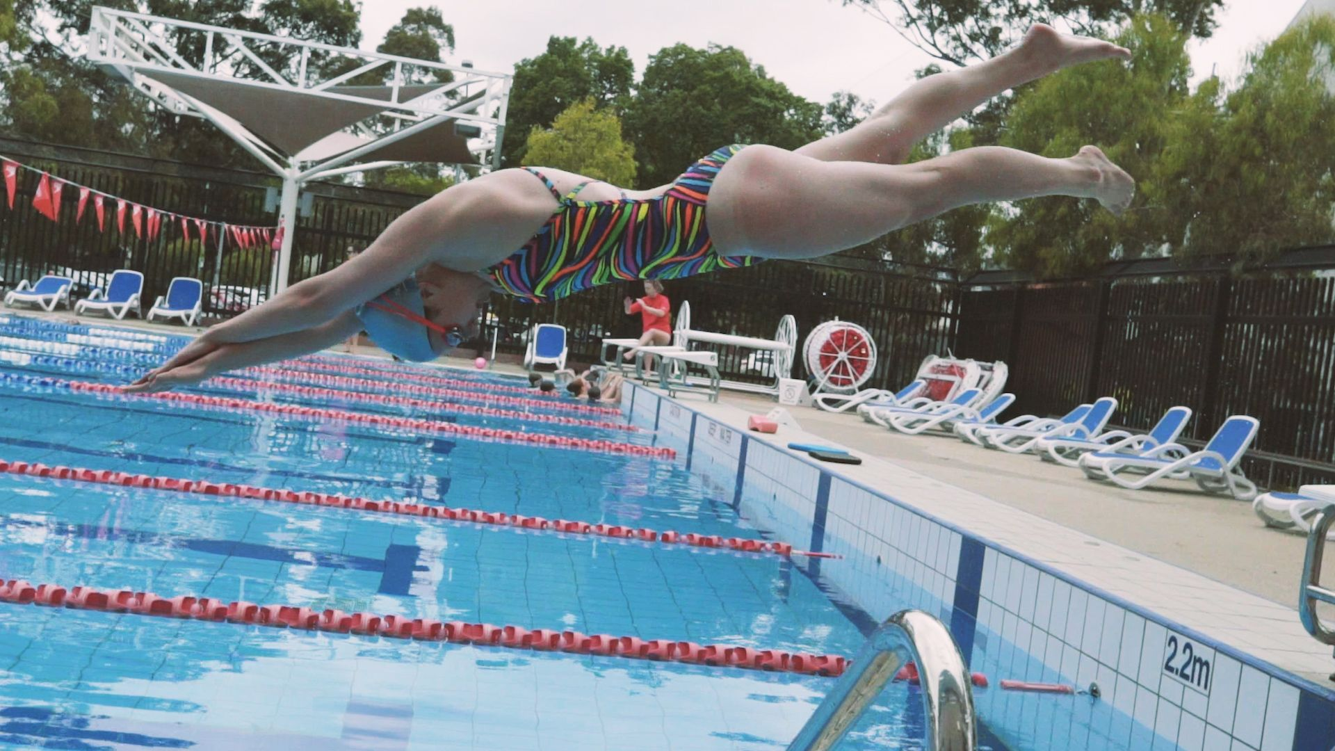 Female student dives into a pool at the open air Hawthorn Aquatic Centre