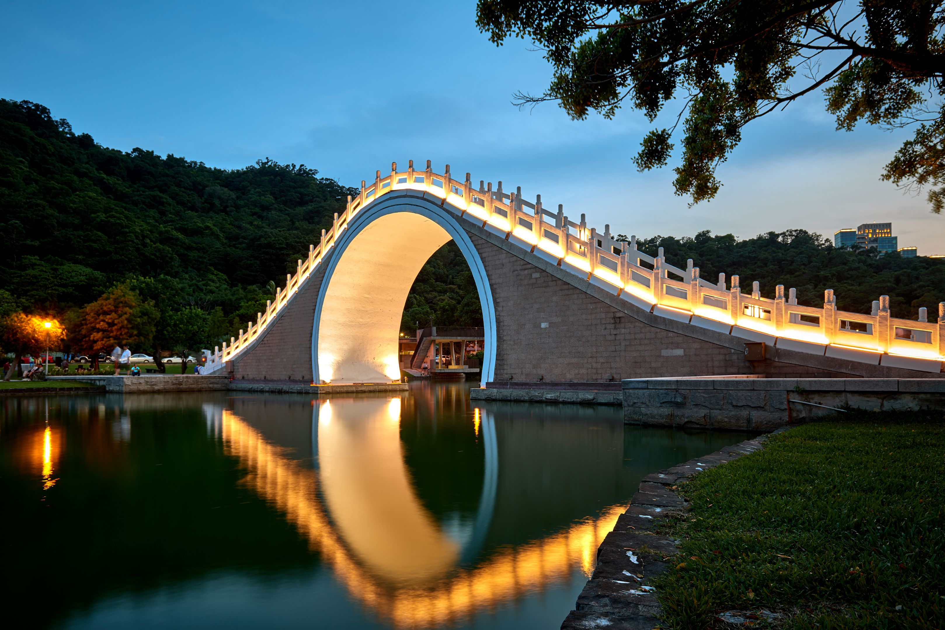 Reflection of the Dahu bridge in the water after the sunset in Taipei Park, Taiwan