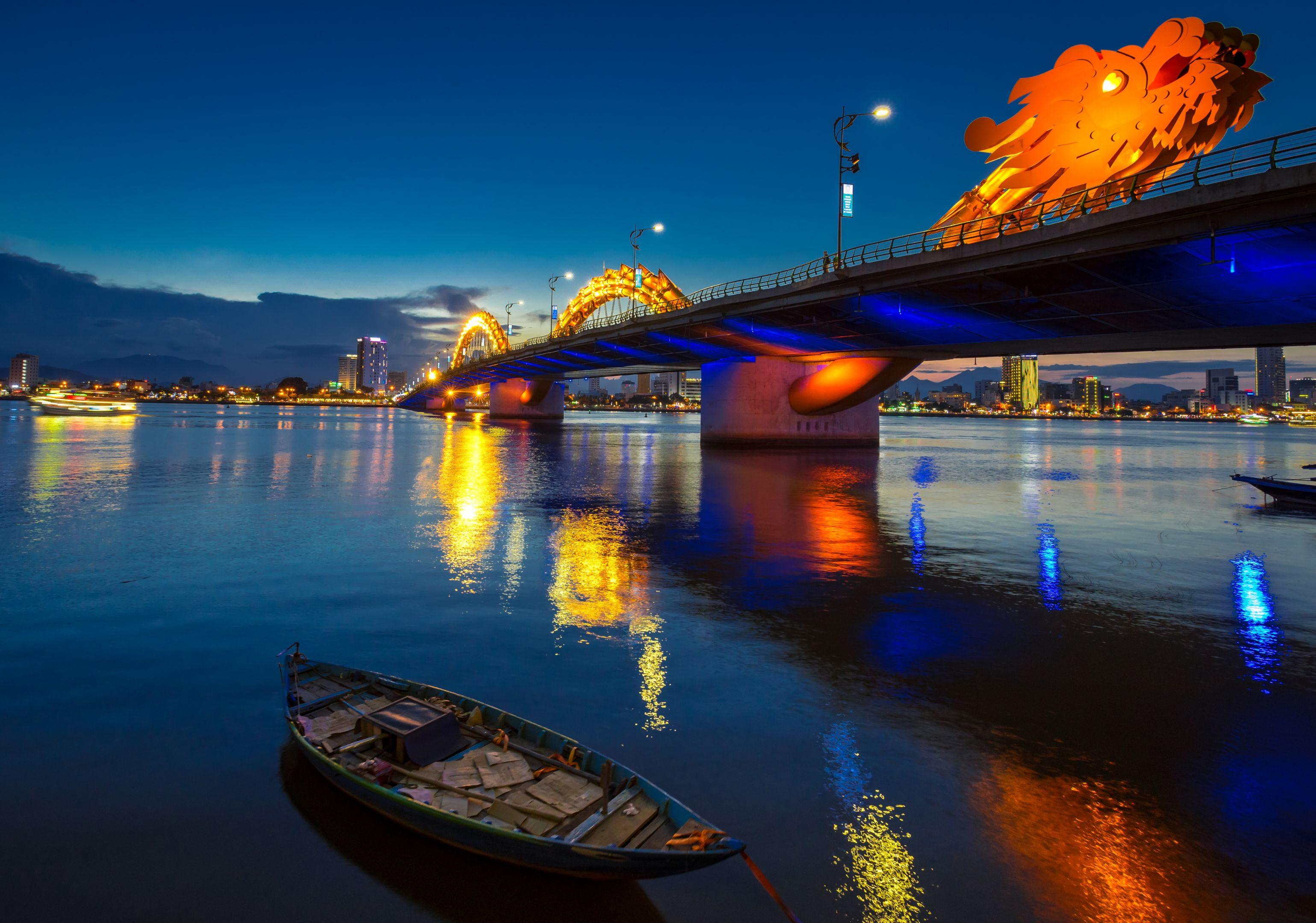 Dragon Bridge in Danang at night, with reflections on the river.