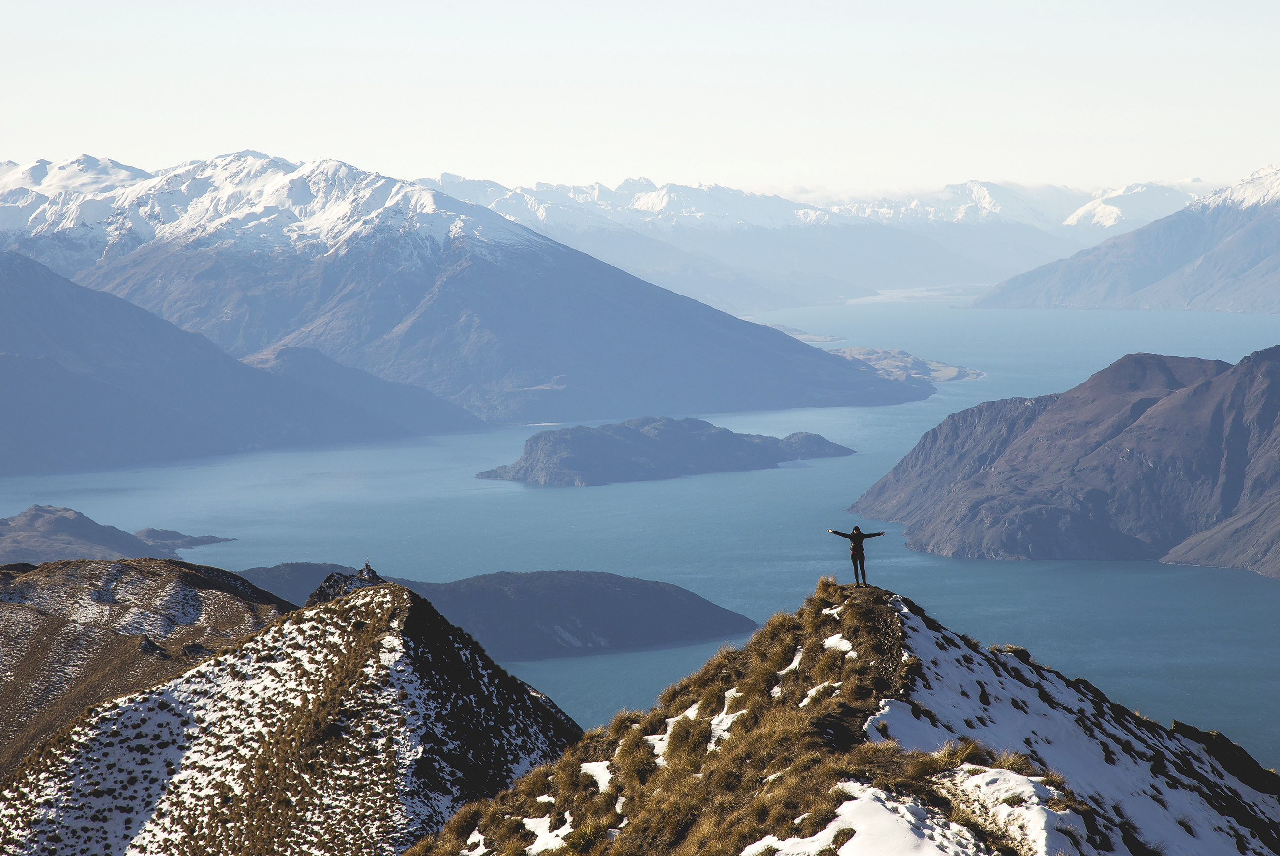 Person stands on a summit peak, arms outstretched, looking out to mountains and the sea.