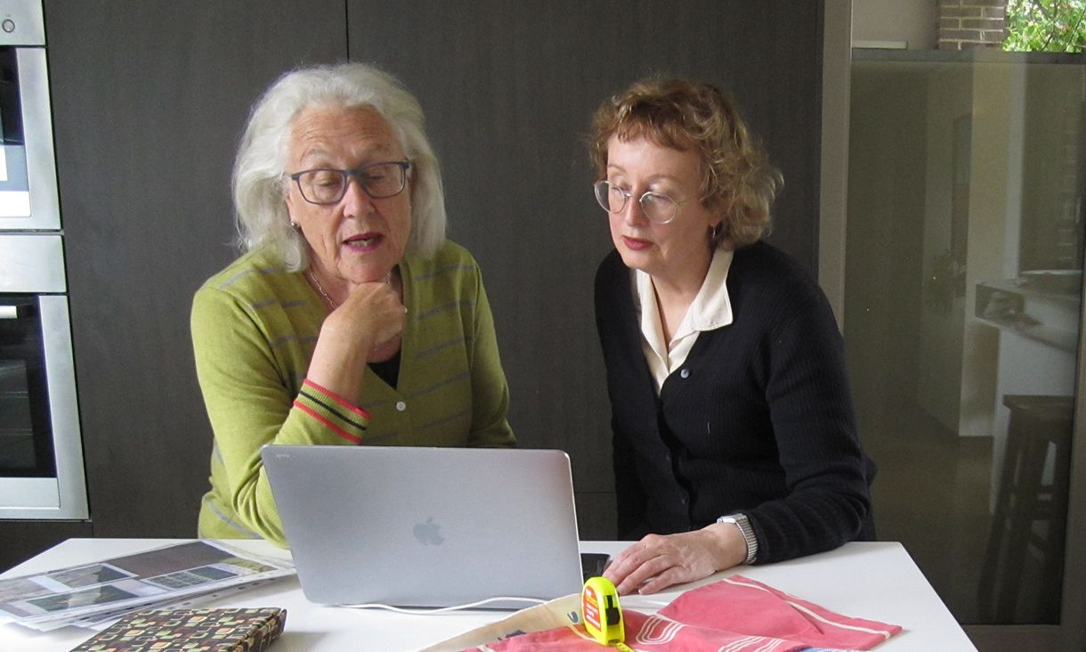 Robyn Oswald-Jacobs and Nanette Carter sit at a desk with a laptop out, collaborating on their research