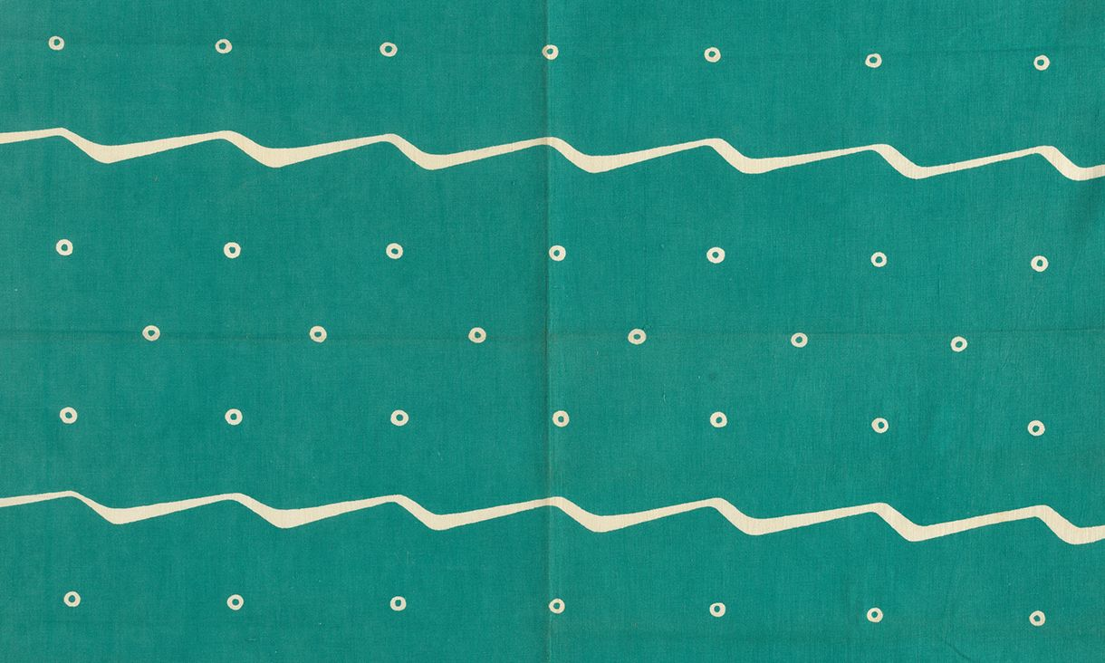 A green and cream print of the sea - waves and spots