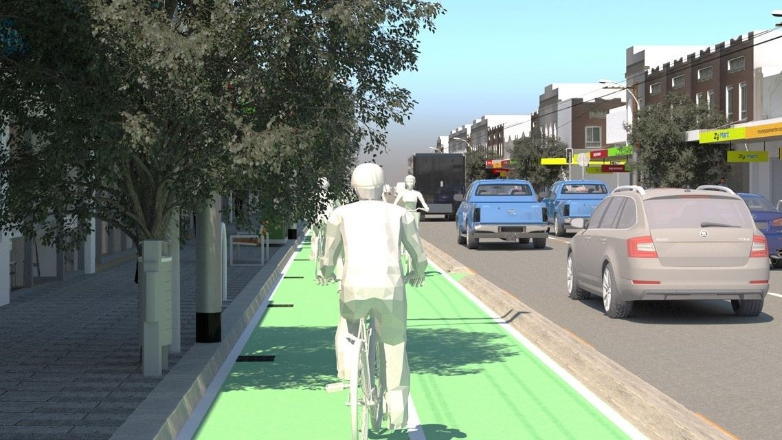 Presented as a virtual reality simulation, an animated figure is riding a bicycle in a bike lane on a city street, with cars driving past.