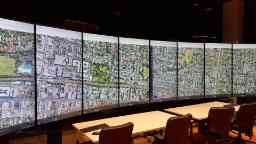 Inside a large room two long tables with four office chairs behind them are set up in front of a wide curving wall of 8 tall screens, all displaying a single image that is an aerial view of houses and streets.