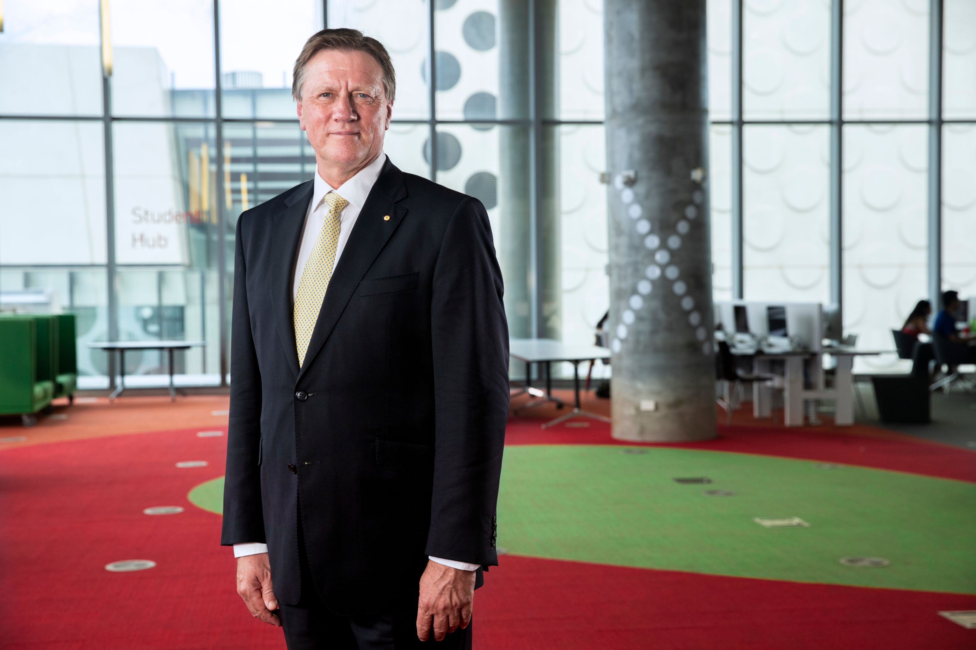 Chancellor of Swinburne stands wearing a suit looking to camera