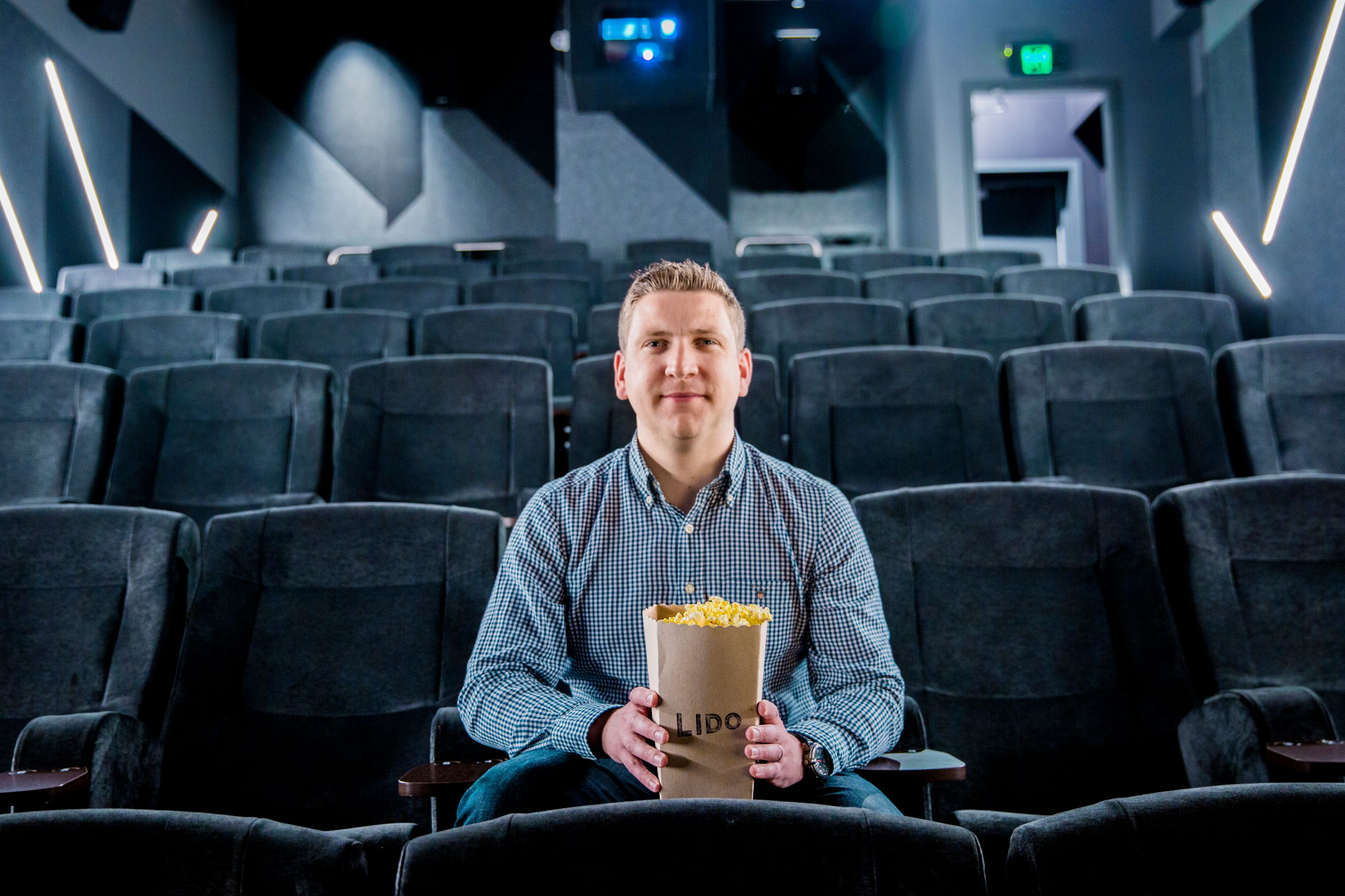 Young man sits in an empty cinema with a bucket of Lido popcorn.