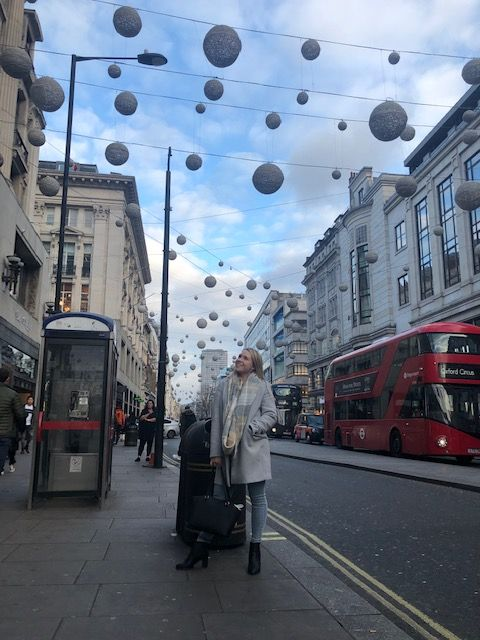 Female standing in a busy London street with Christmas decorations overhead