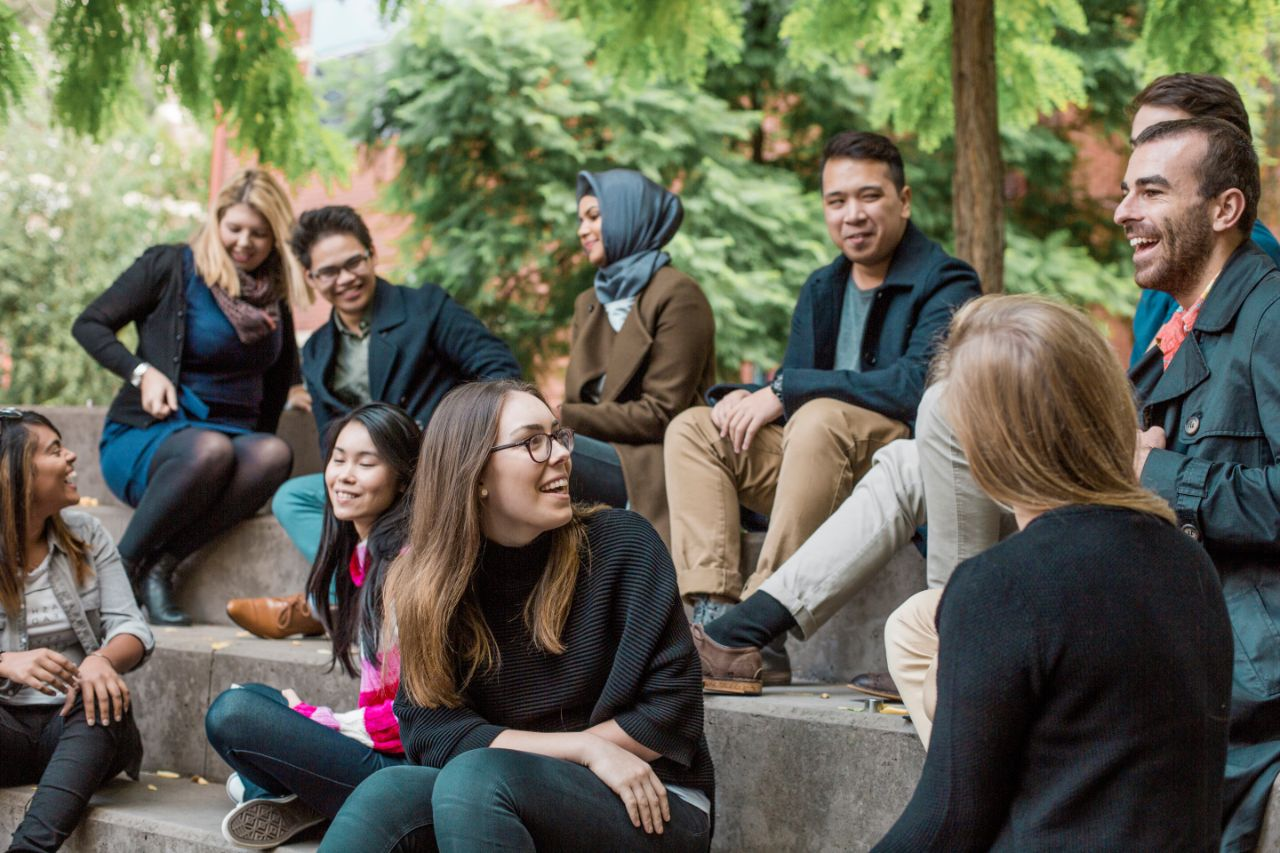 Group of students socialising outside on steps laughing