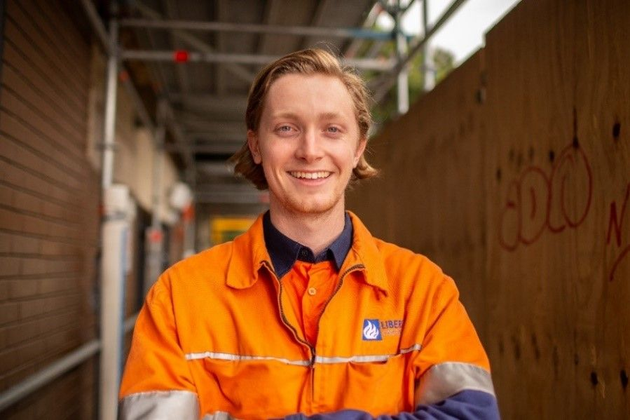 A smiling young man wearing an orange high-vis work shirt stands in front of a construction site