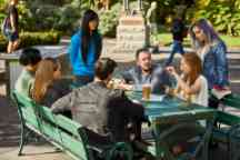 A group of students sit at a table outside chatting