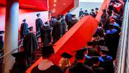Students dress in graduation regalia line the steps as they wait to walk on stage