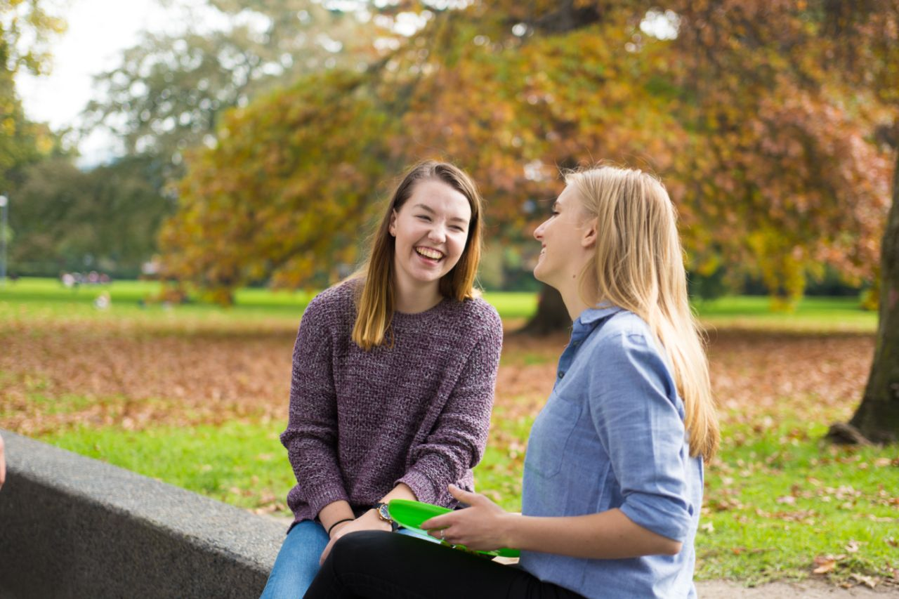 Two students socialising in the park with a frisbee