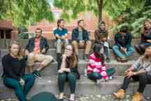 Student ambassadors sit at the steps outside on campus and socialise