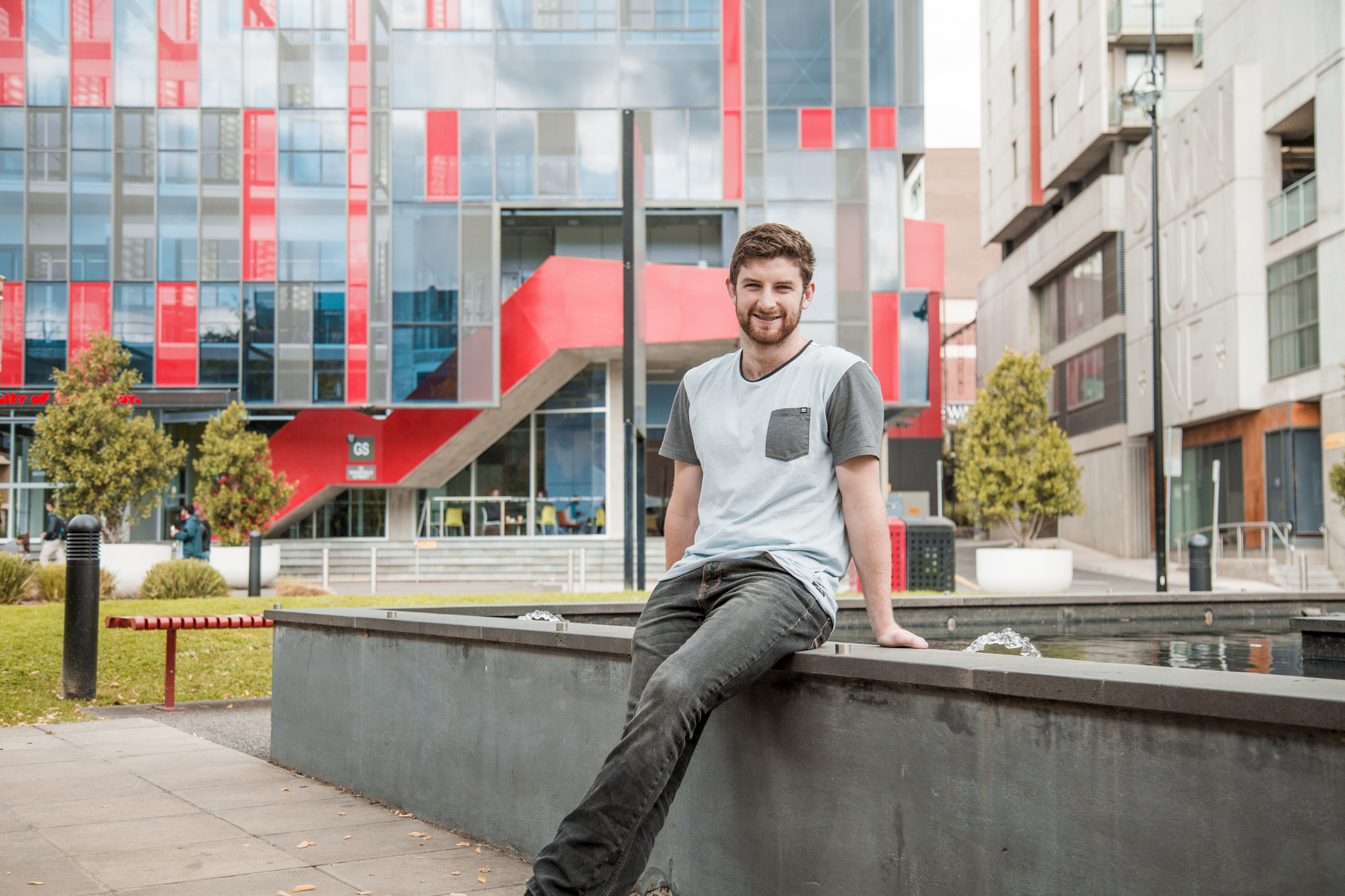 Male student ambassador sits outside in the Hawthorn campus sitting on water feature