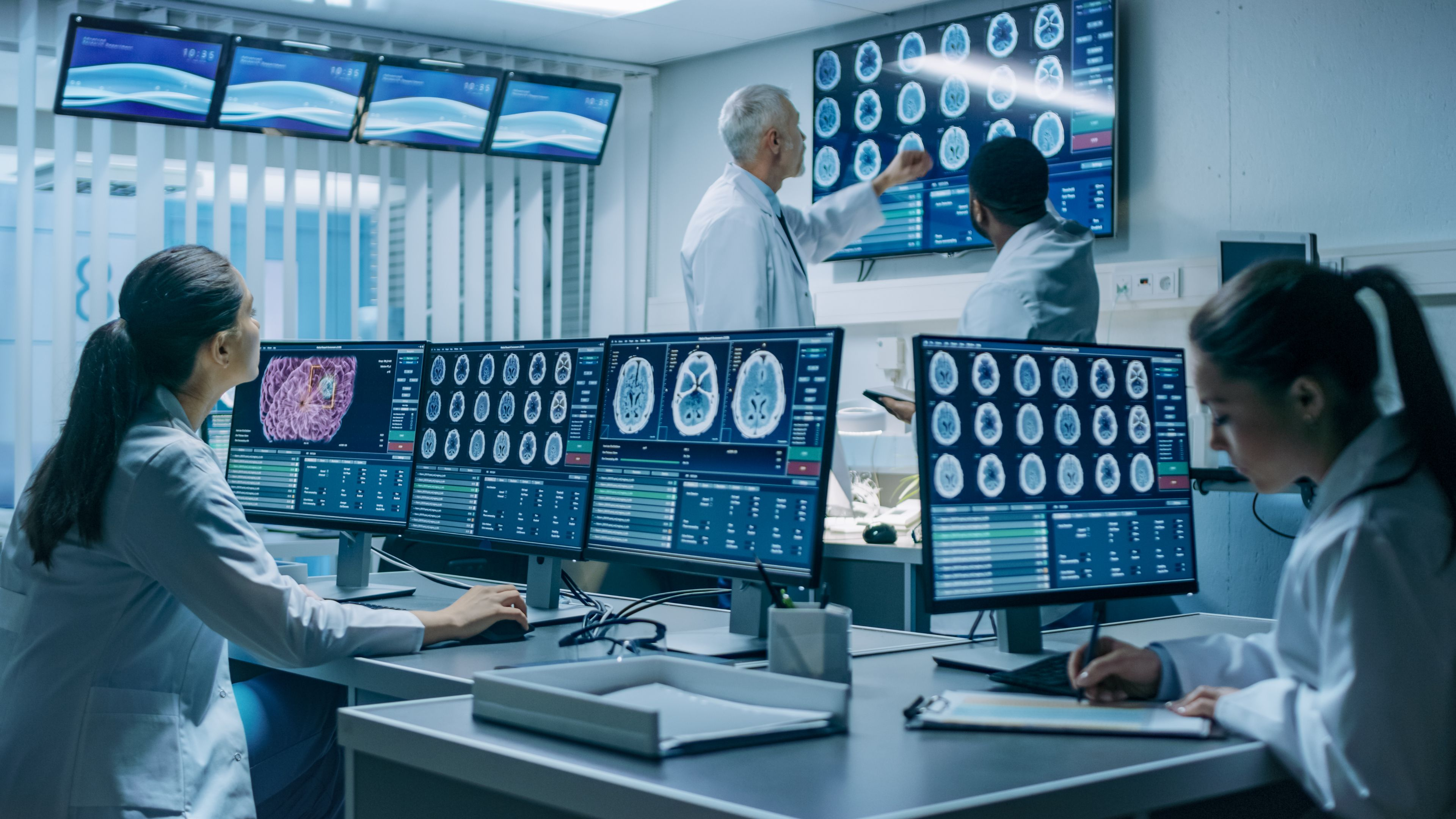 Neurologists / neuroscientists surrounded by monitors showing CT, MRI scans having discussions.