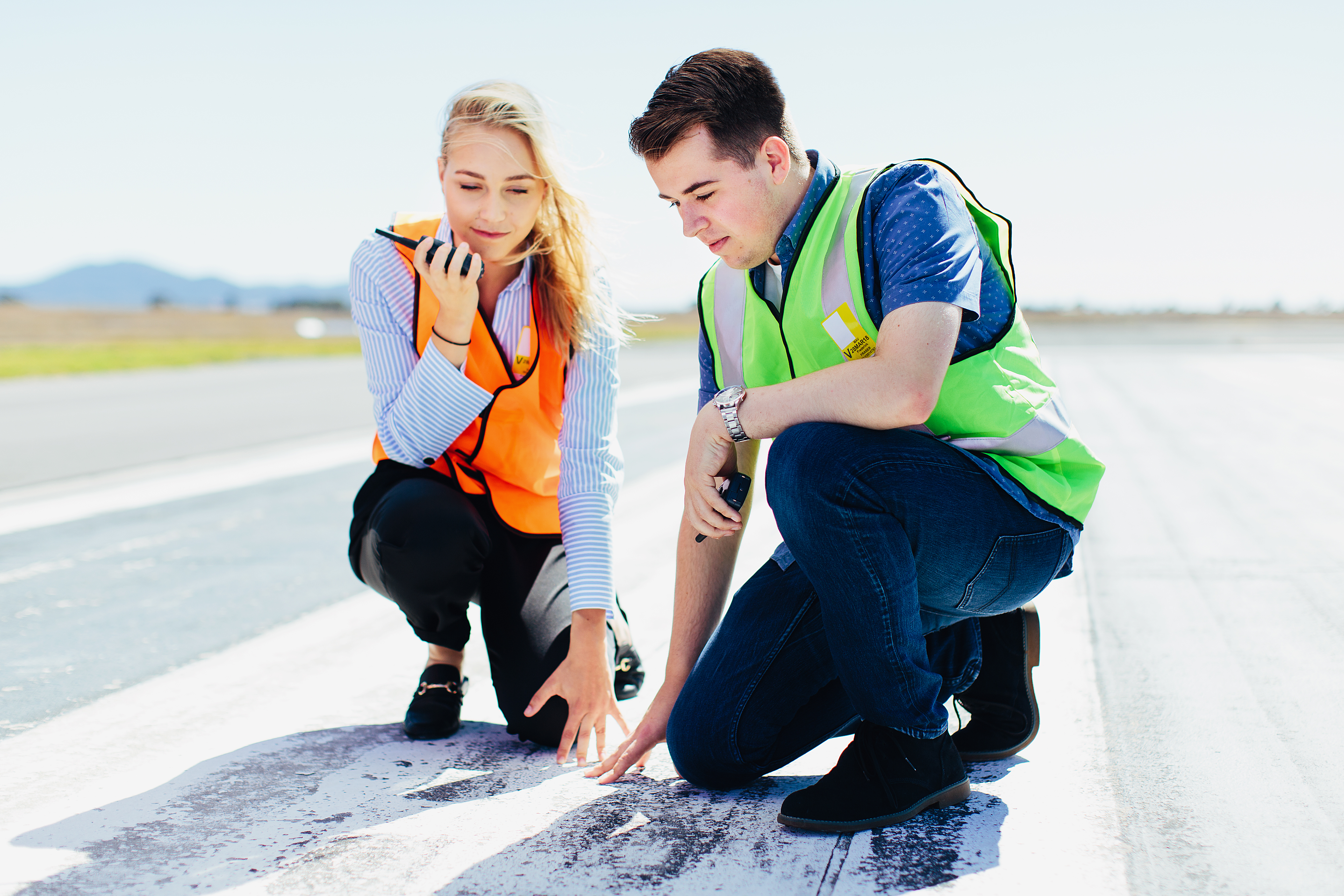 Two aviation management students inspect a runway for cracks wearing high vis jackets talking into a radio
