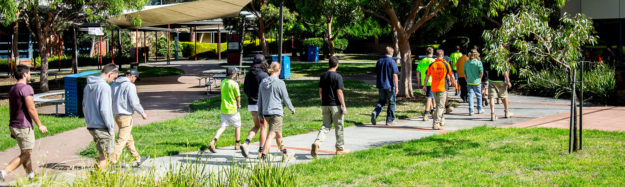 Image of the Swinburne University Croydon campus, showing students walking across path outdoors.