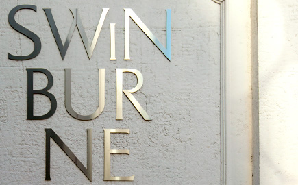 Close up of silver Swinburne logo against white building