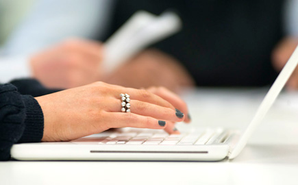 This is a close up image of a person working on a laptop showing the side view of the users hands and the laptop.