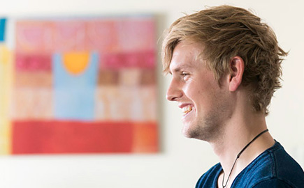 Image of a student in a student accommodation room with artwork in the background